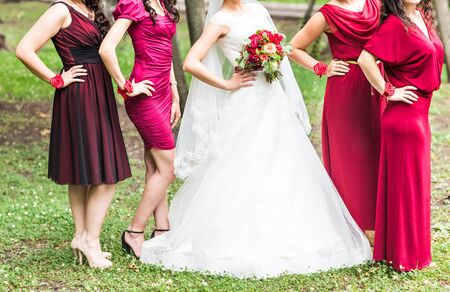 bridesmaids: Bride with bridesmaids on the park on the wedding day. Stock Photo