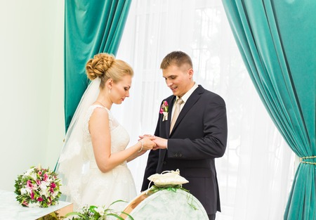 put together: Bride slipping ring on finger of groom at wedding. Stock Photo