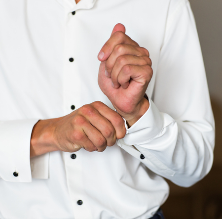 cuffs: Sexy man buttons cuff-link on French cuffs sleeves luxury white shirt Stock Photo