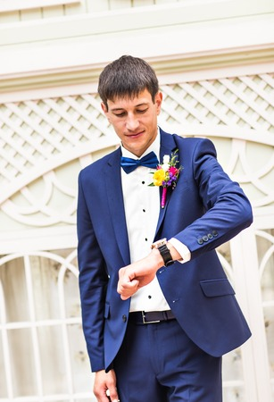 winding up: Groom with the clock on the hand outdoors Stock Photo