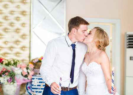 happy moment: stylish gorgeous happy bride and groom kissing at wedding reception, emotional cheerful moment. Stock Photo