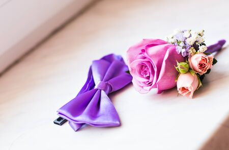 boutonniere: Gentle grooms boutonniere and bow-tie. Wedding accessories for a groom