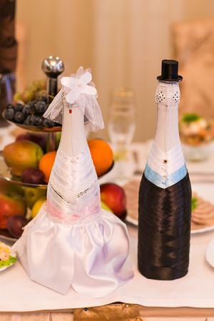 Champagne bottles decorated as a bride and groom.