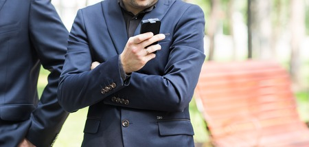 mobile sms: Young urban professional man using smart phone. Businessman holding mobile smartphone using app texting sms message. Stock Photo