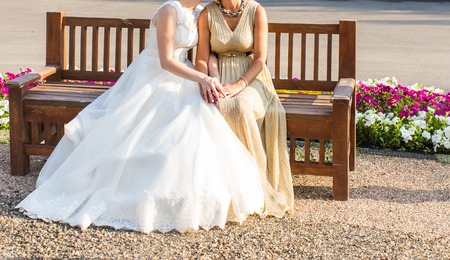 mother on bench: Bride With Mother sitting on a bench outdoors.