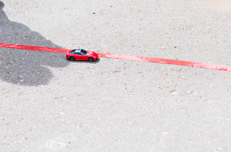 speedster: toy red car outdoors. small car on the road