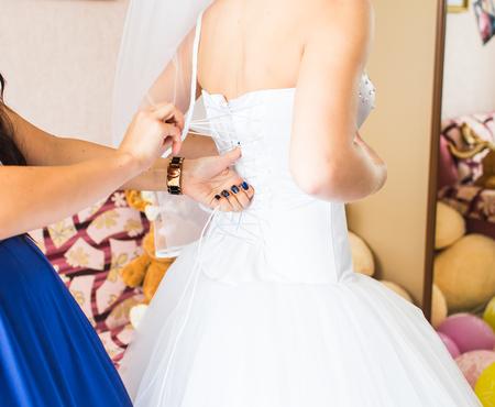 bridesmaid: Bridesmaid is helping the bride to dress.