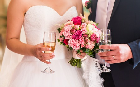 Bride and groom holding wedding champagne glasses close-up.