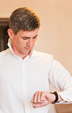 retardation: Businessman looking at the time on his wrist watch