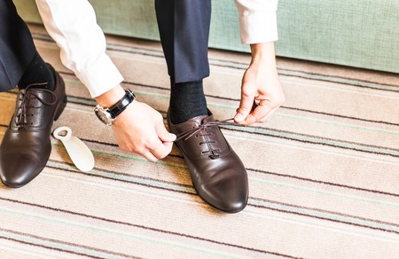 men s feet: A young man tying elegant shoes indoors. Stock Photo