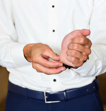 sleeve: Business man fastening buttons on shirt sleeve at home.