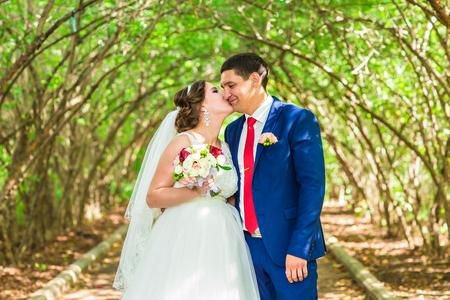 Mariée et le marié au jour de mariage marchant à l'extérieur sur la nature de printemps. Couple de mariée, Happy Newlywed femme et homme embrassant dans le parc verdoyant. Couple de mariage amoureux en plein air. Mariée et le marié