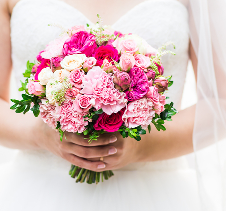 Beautiful wedding bouquet in hands of the bride.