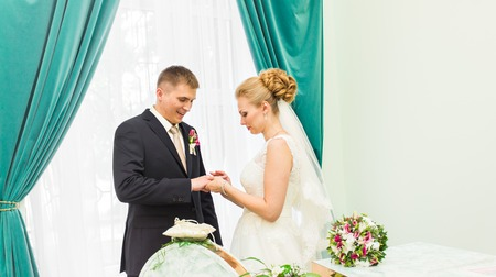 fingers put together: Bride slipping ring on finger of groom at wedding. Stock Photo