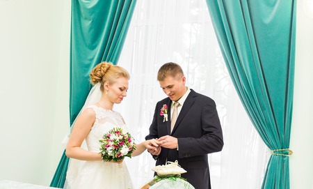 put together: Groom slipping ring on finger of bride at wedding.