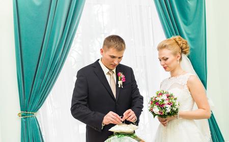fingers put together: Groom slipping ring on finger of bride at wedding.