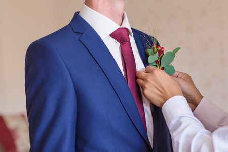 wedding customs: groom getting ready for the wedding. Best Man Adjusting Grooms Boutonniere Stock Photo