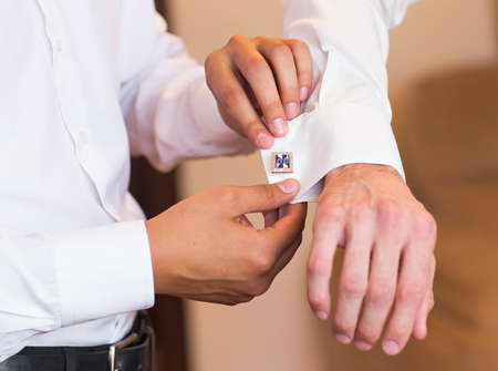 cuff links: Groomsman helps to groom to put on cufflinks