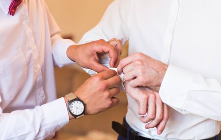 cufflink: Groomsman helps to groom to put on cufflinks
