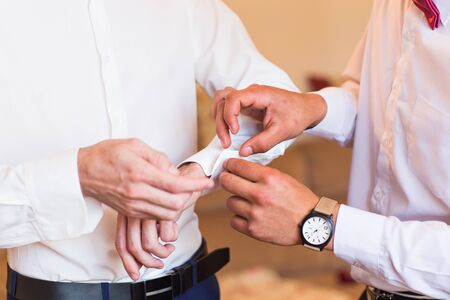 cufflinks: Groomsman helps to groom to put on cufflinks