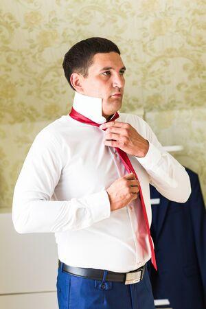 unbutton: Closeup portrait of  handsome businessman in suit putting on necktie indoors.