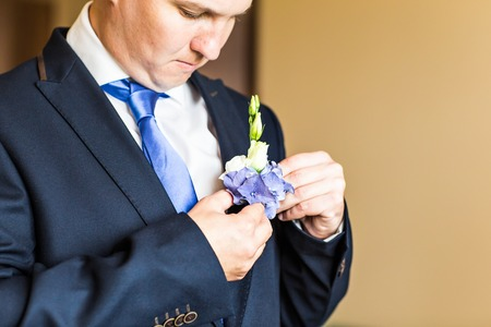 boutonniere: Wonderful wedding boutonniere on a costume of groom.