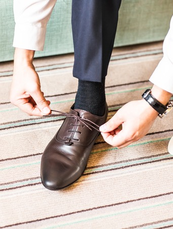A young man tying elegant shoes indoors. Stock Photo