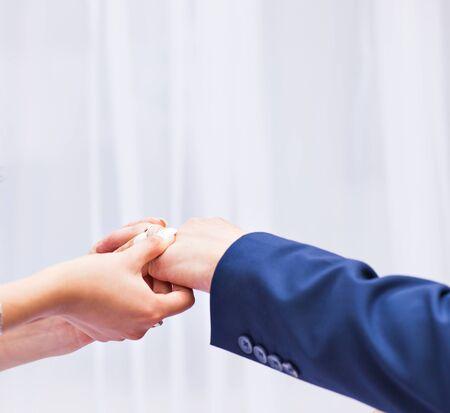 fingers put together: Bride putting a wedding ring on grooms finger.
