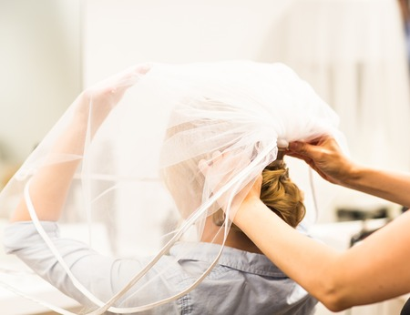 chignon: Stylist pinning up a brides hairstyle and bridal veil before the wedding.