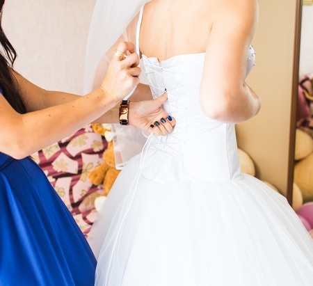 bodice: Bridesmaid is helping the bride to dress.