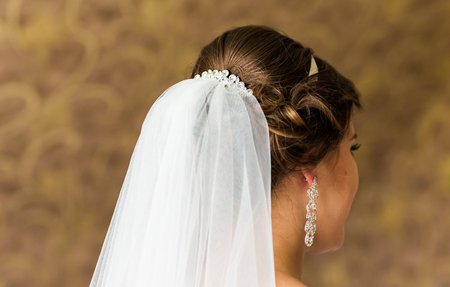 pinning: Stylist pinning up a brides hairstyle and bridal veil before the wedding.