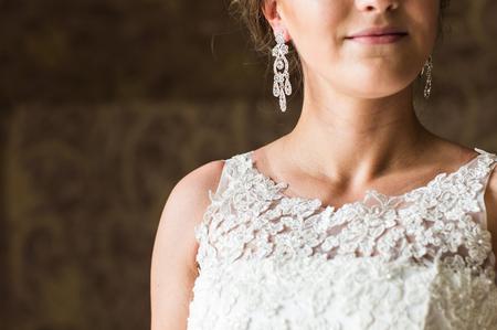 diamond earrings: close up of beautiful woman wearing shiny diamond earrings.
