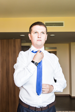 unbutton: Portrait of  handsome businessman in suit putting on necktie indoors.