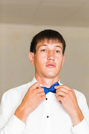 unbutton: Closeup portrait of  handsome businessman in suit putting on bow-tie indoors Stock Photo