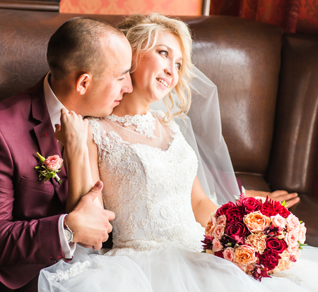 lap of luxury: Bride and groom sitting  in a luxurious chair. Loving couple together indoors