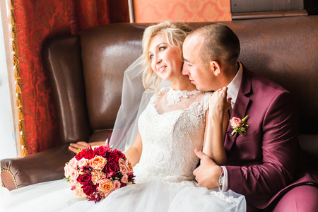 luxurious: Bride and groom sitting  in a luxurious chair. Loving couple together indoors