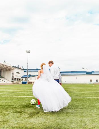 winning pitch: European Football Championship concept. Wedding couple on the football stadium