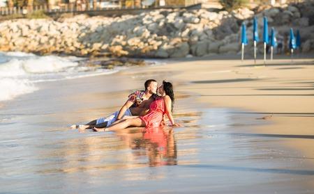 pareja apasionada: Los pares apasionados jovenes que se besan en la arena.
