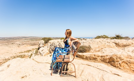 body consciousness: young beautiful caucasian female on a cliff above the sea.