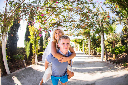 man carrying woman: Happy couple. Man carrying woman on his back. Stock Photo