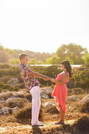 mujer mirando el horizonte: Pareja joven de la mano y mirando el uno al otro en un d�a soleado de verano