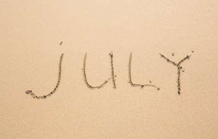 meses del año: Julio - escrito en la arena en la playa textura, meses serie del año.