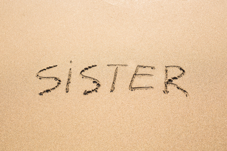 girl drawing: Sister word handwritten on a sand of beach.
