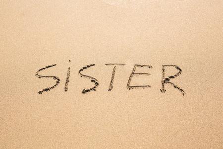 drawing boy: Sister word handwritten on a sand of beach.
