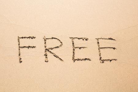 Free word handwritten in sand on sunny summer beach