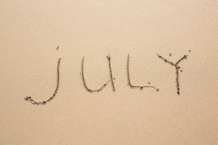 months of the year: July - written in sand on beach texture, months year series.