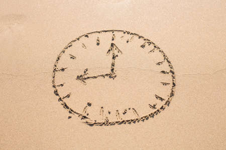 sandy: Picture of a clock face on a sandy beach. Time concept