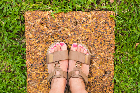 upper floor: Feet selfie from upper view of a woman traveler in sandal during a tour trip around the world. Souvenir photo of multicolor museum floor made of small tiles. Tourist take a photo of her own leg. Stock Photo