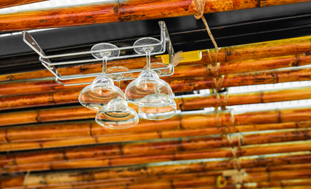 barware: Clean stemware hanging on the rack in the bar. Stock Photo