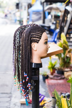 mannequin head: Female mannequin head with braided pigtails hairstyle decorated with beads, relaxing on the beach